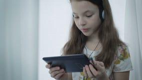 Niña hermosa con los auriculares que mira los vídeos divertidos en la tableta y risas almacen de video