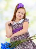 Niña hermosa con un ramo de flores azules Fotos de archivo libres de regalías
