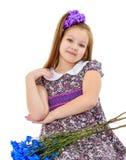 Niña hermosa con un ramo de flores azules Imágenes de archivo libres de regalías