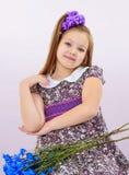 Niña hermosa con un ramo de flores azules Fotografía de archivo libre de regalías