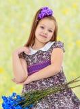 Niña hermosa con un ramo de flores azules Fotografía de archivo