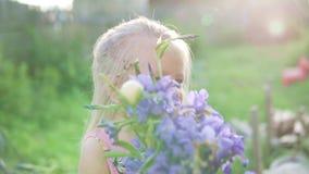 Niña hermosa con un ramo de soportes azules de las campanas en el jardín almacen de video
