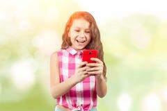 Niña hermosa con un smartphone imágenes de archivo libres de regalías