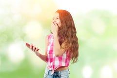 Niña hermosa con un smartphone foto de archivo libre de regalías