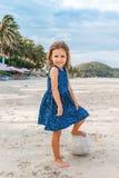Niña hermosa con una bola en la playa foto de archivo