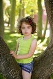 Niña hermosa de los ojos azules en el árbol del parque Fotografía de archivo libre de regalías