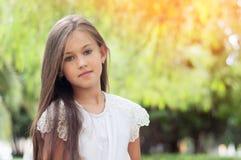 Niña hermosa en el parque, con el pelo largo y y un swee fotos de archivo