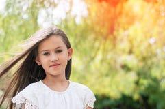 Niña hermosa en el parque, con el pelo largo y y un swee foto de archivo libre de regalías