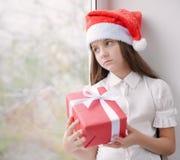 Niña hermosa en el sombrero de Papá Noel que sostiene en manos una caja con C Foto de archivo