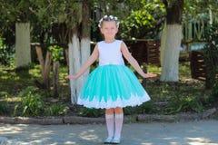 niña hermosa en el vestido que se coloca y que presenta sobre el fondo de la naturaleza, niño con una guirnalda de flores artific Fotografía de archivo libre de regalías