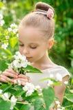 Niña hermosa en un vestido blanco que presenta en la hierba Fotos de archivo libres de regalías