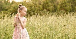 Niña hermosa en un vestido blanco que presenta en la hierba Imagen de archivo libre de regalías