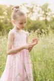 Niña hermosa en un vestido blanco que presenta en la hierba Fotografía de archivo libre de regalías