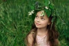 Niña hermosa en un vestido blanco que presenta en la hierba Imágenes de archivo libres de regalías