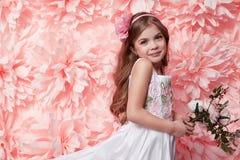 Niña hermosa en vestido lindo con la flor Imagen de archivo