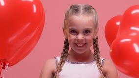 Niña hermosa que aparece detrás de los globos rojos, sorpresa de día de San Valentín almacen de metraje de vídeo