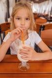 Niña hermosa que bebe un batido de leche Foto de archivo