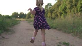 Niña hermosa que corre a través del campo en la puesta del sol metrajes