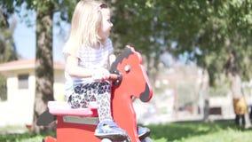 Niña hermosa que juega el caballo de madera en el patio