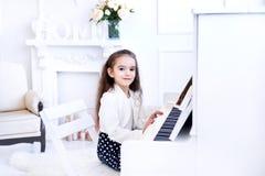 Niña hermosa que juega el piano en la sala de estar blanca Imagen de archivo libre de regalías