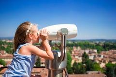 Niña hermosa que mira binocular de fichas en terraza la pequeña ciudad en Toscana, Italia Foto de archivo libre de regalías