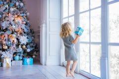 Niña hermosa que mira hacia fuera la ventana Árbol de navidad Li fotografía de archivo