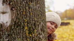 Niña hermosa que oculta detrás de árbol en otoño almacen de metraje de vídeo