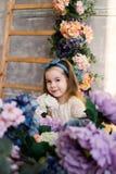Niña hermosa que presenta con un ramo grande de flores adentro Imagen de archivo