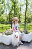 Niña hermosa que se sienta en banco en parque con su perro blanco adorable de Pomeranian foto de archivo libre de regalías