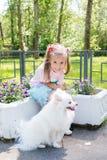 Niña hermosa que se sienta en banco en parque con su perro blanco adorable de Pomeranian fotografía de archivo libre de regalías