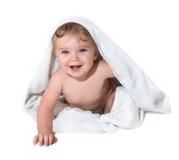 Niña hermosa que sonríe debajo de la toalla imagen de archivo libre de regalías