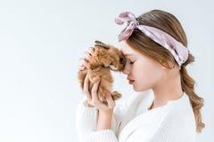 Niña hermosa que sostiene el conejo peludo aislado en blanco Imagen de archivo