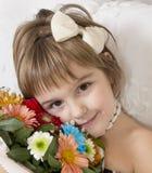 Niña hermosa que sostiene las flores Foto de archivo libre de regalías