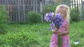 Niña hermosa que sostiene un ramo de flores azules y de risa metrajes