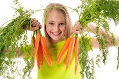 Niña hermosa que sostiene zanahorias Imagenes de archivo