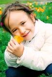 Niña inocente con una flor a disposición Foto de archivo libre de regalías
