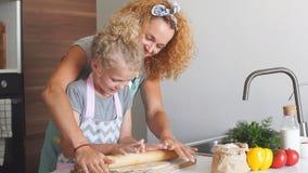 Niña joven que ayuda a su madre a preparar el pan para el día de fiesta almacen de metraje de vídeo