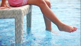 Niña joven que hace que el agua salpica con sus piernas y que se divierte cerca de piscina almacen de metraje de vídeo