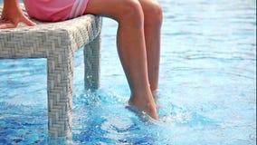 Niña joven que hace que el agua salpica con sus piernas y que se divierte cerca de piscina metrajes