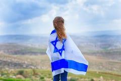 Niña judía israelí con la opinión trasera de la bandera de Israel imagenes de archivo