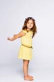 Niña juguetona en la sonrisa amarilla del vestido Fotos de archivo libres de regalías