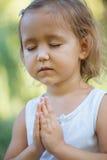 Niña linda 4 - 5 años que meditan en el parque verde del verano en loto presentan Imagen de archivo