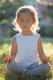Niña linda 4 - 5 años que meditan en el parque verde del verano en loto presentan Fotos de archivo