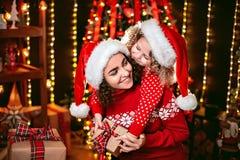 Niña linda alegre y su más vieja hermana que intercambian los regalos imágenes de archivo libres de regalías