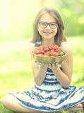 Niña linda con el cuenco lleno de fresas frescas Pre - muchacha adolescente con los vidrios y los dientes - apoyos dentales Imagen de archivo