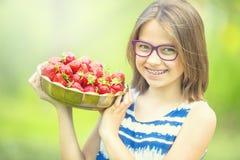 Niña linda con el cuenco lleno de fresas frescas Pre - muchacha adolescente con los vidrios y los dientes - apoyos dentales Imágenes de archivo libres de regalías