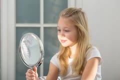 Niña linda con el lápiz labial que aplica maquillaje Imagenes de archivo