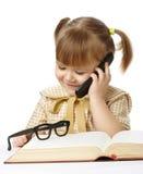 Niña linda con el libro que habla con un teléfono celular Foto de archivo libre de regalías