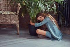 Niña linda con el pelo marrón largo que lleva un vestido elegante, sentándose en un piso de madera en un cuarto con un interior d Imágenes de archivo libres de regalías
