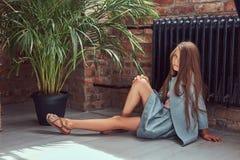Niña linda con el pelo marrón largo que lleva un vestido elegante, sentándose en un piso de madera en un cuarto con un interior d Foto de archivo libre de regalías